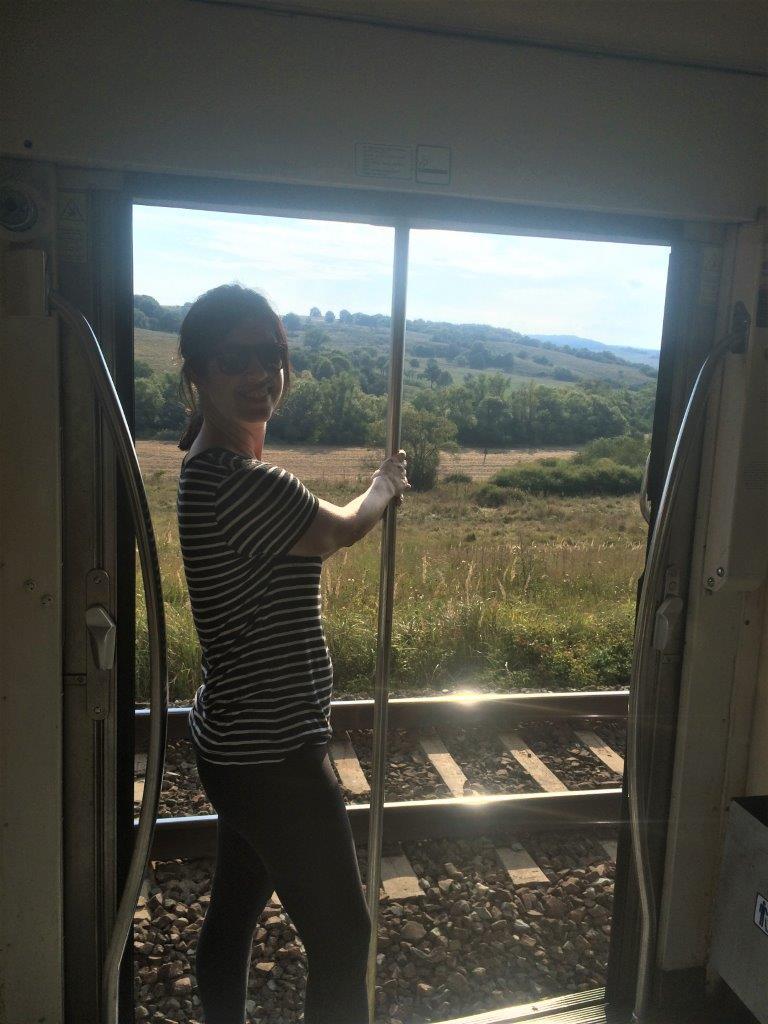 woman standing in doorway of moving train