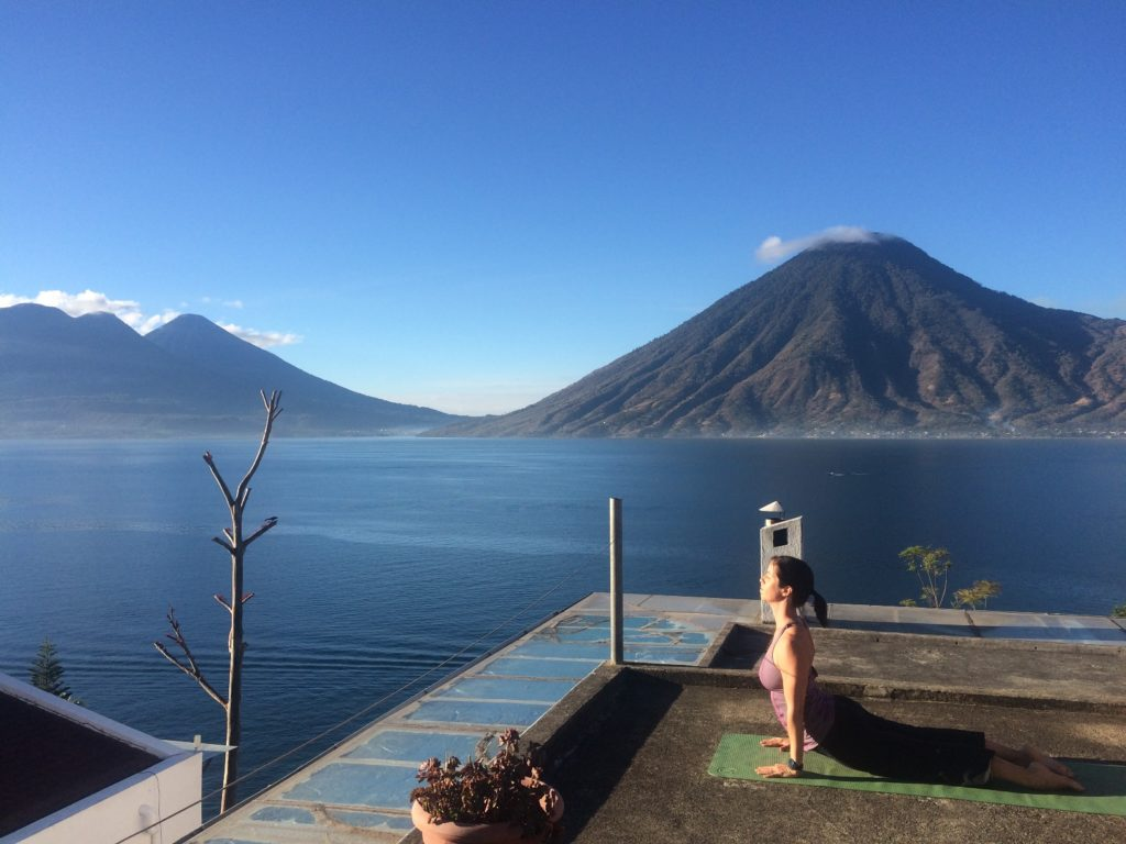 Woman doing yoga on a rooftop with views of Lake Atitlan and the volcanoes