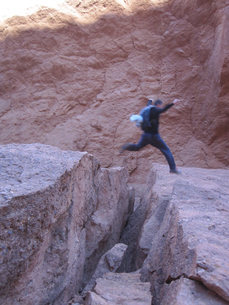 Hiker jumping over canyon in budget destination Morocco