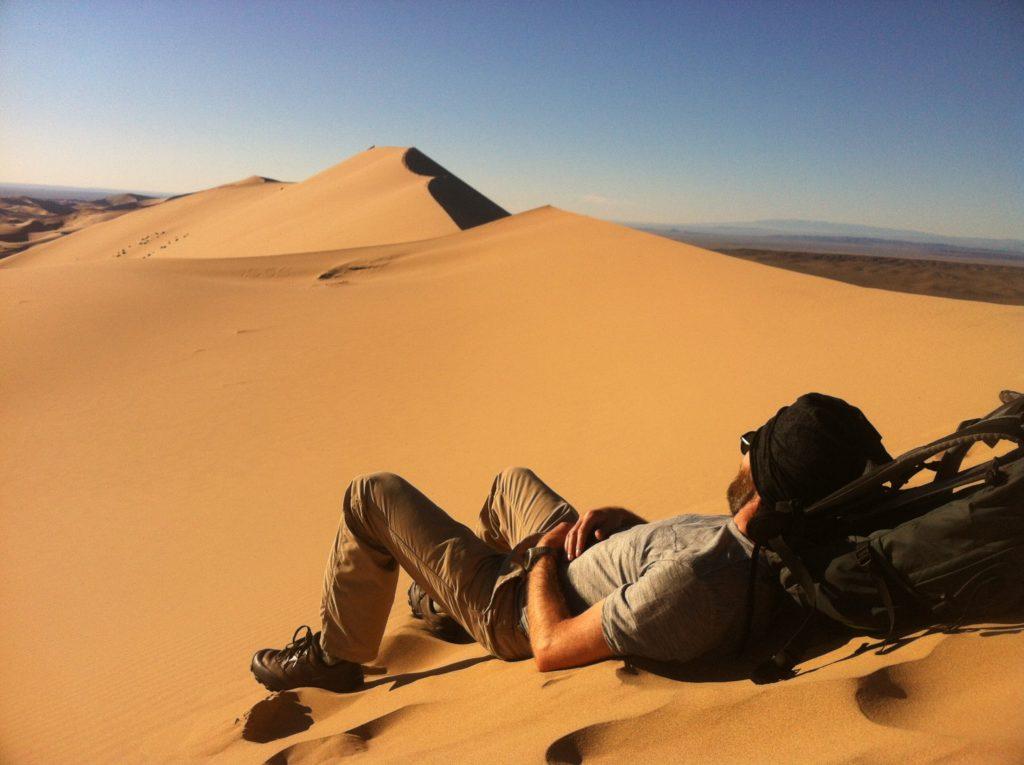 Budget traveler resting on sand dune in Mongolia