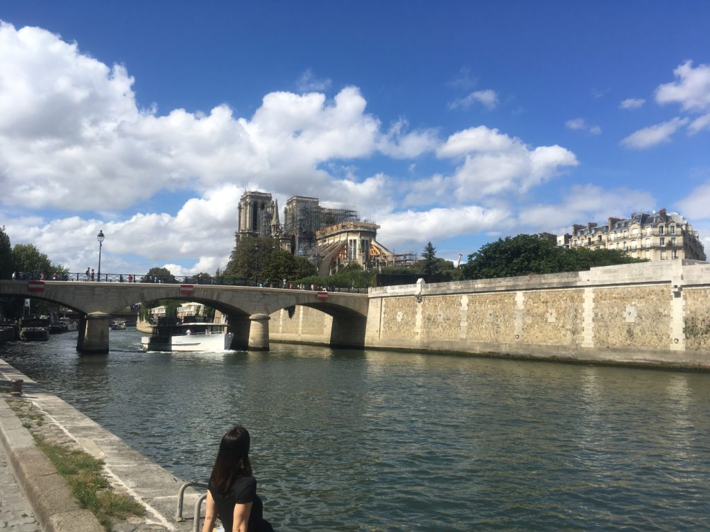 Woman on river looking at Notre Dame