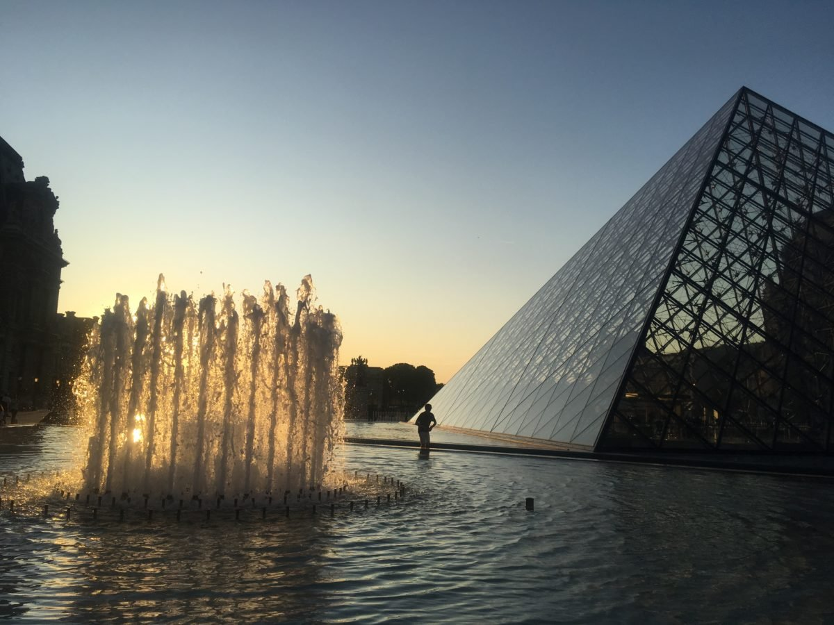 The Louvre pyramid and fountain at sunset in Paris