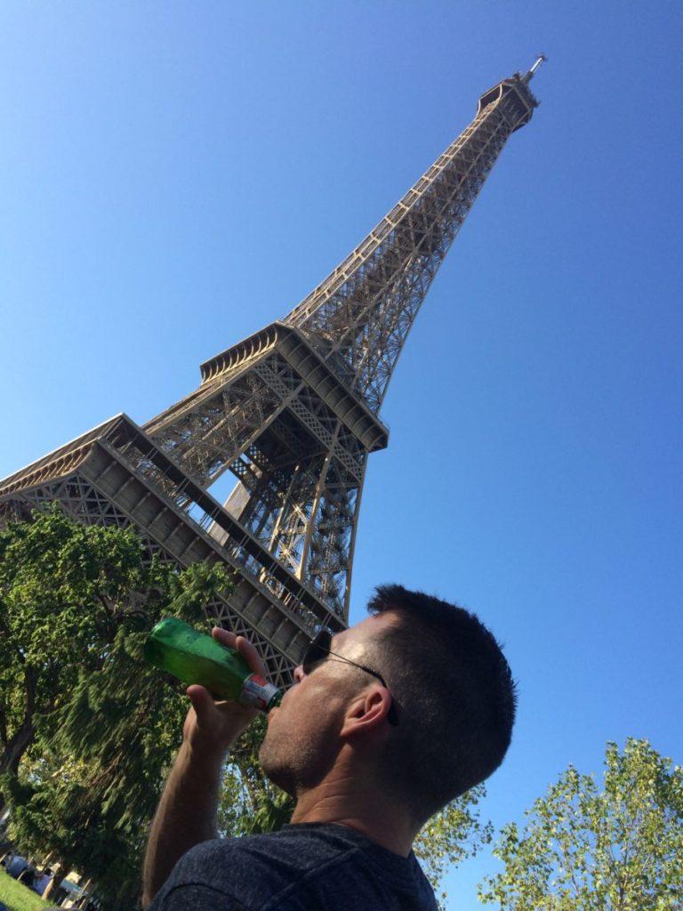 Man drinking beer near Eiffel Tower