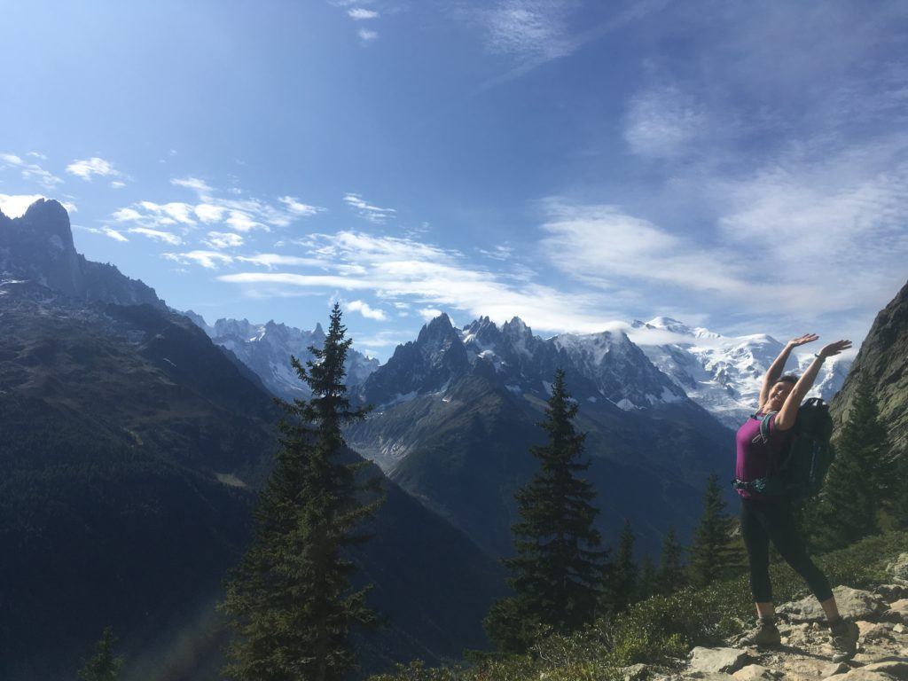 Woman with arm in the air in front of mountains on the Tour du Mont Blanc hike