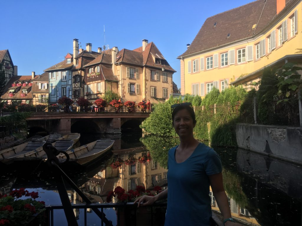 Woman in front of canal and boats in Colmar