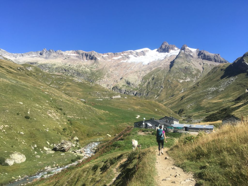 Woman hiking next to horse to Refuge des Mottets