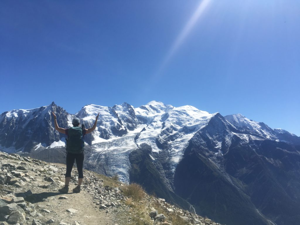 Woman on Tour du Mont Blanc hike overlooking snow capped mountains