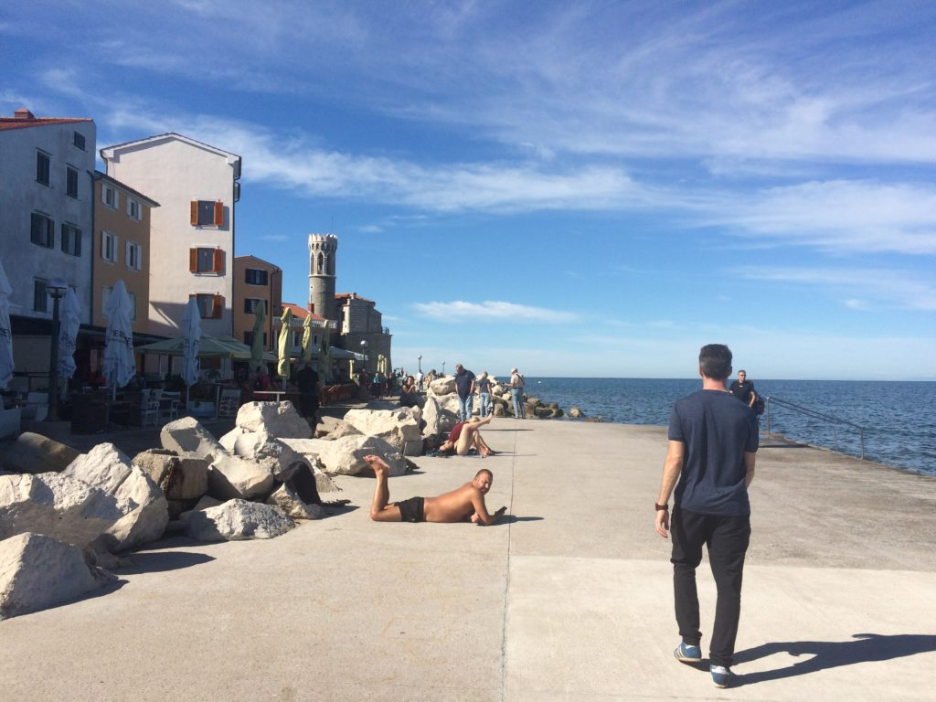 Man sunbathing on the Piran promenade