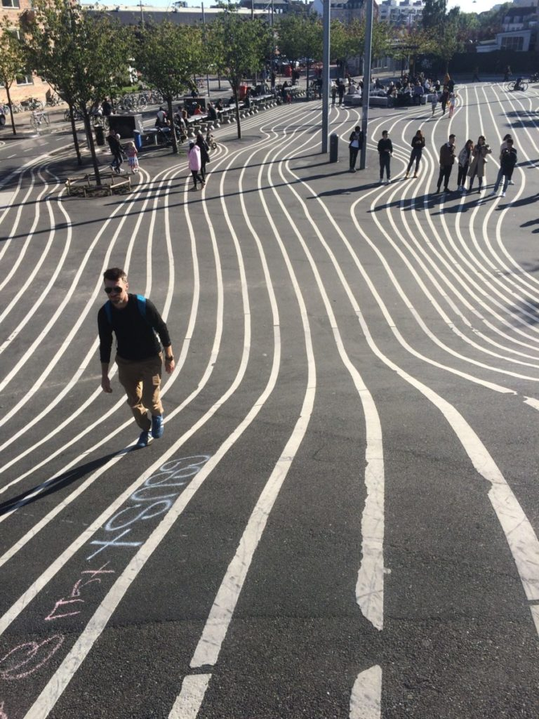 Man walking up striped hill in Superkilen Park in Copenhagen