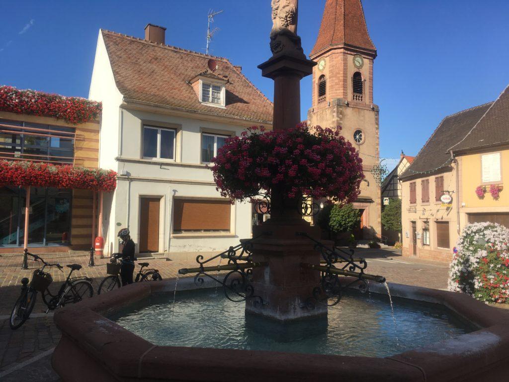Fountain, church and bikes in Wettolsheim
