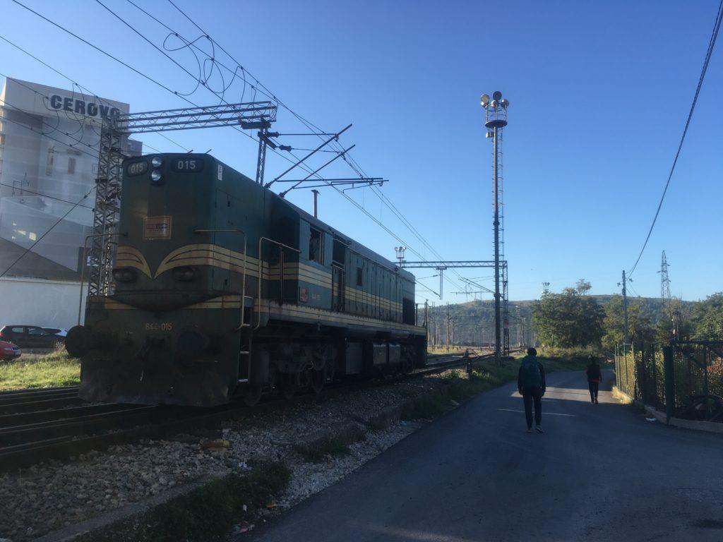 Woman walking next to a train