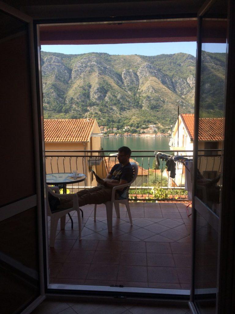 Man lounging on balcony overlooking Kotor Bay