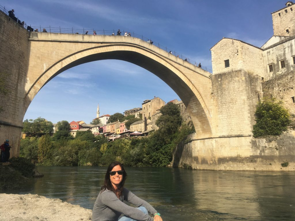 Girl posing by river in front of Old Bridge in Mostar