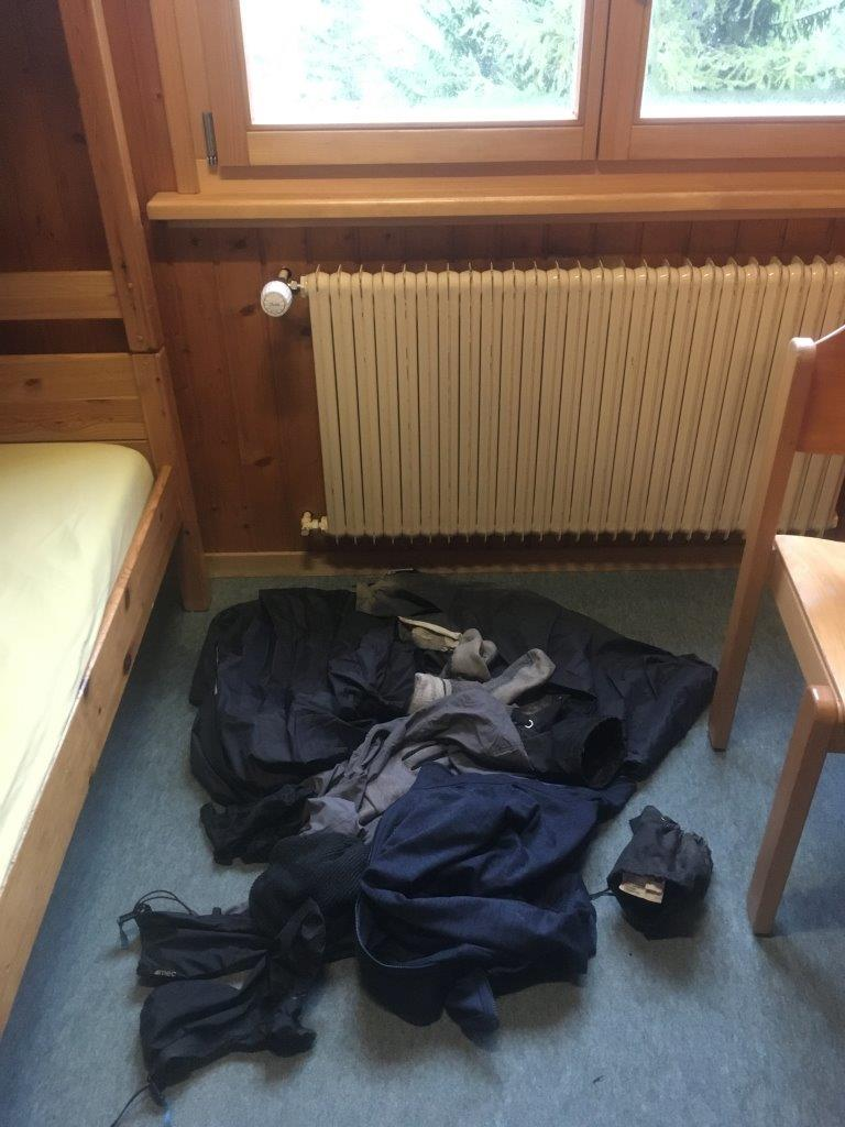 Wet rain gear on the floor showing how it is an important part of a Tour du Mont Blanc packing list