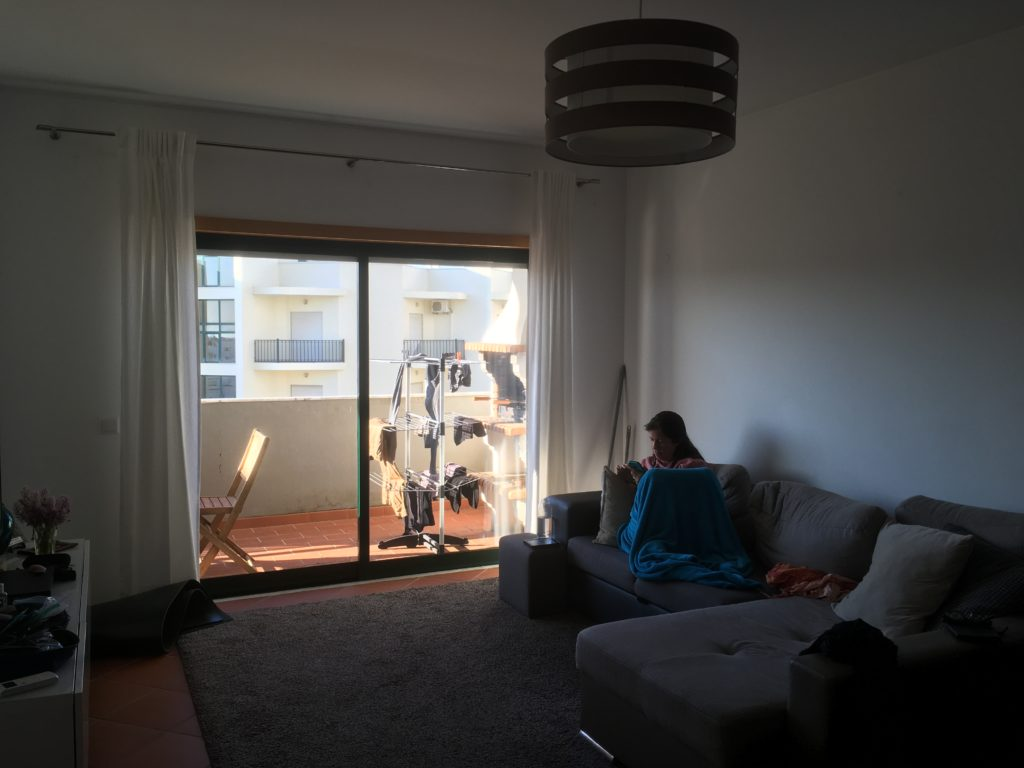 Woman reading in an apartment with a balcony