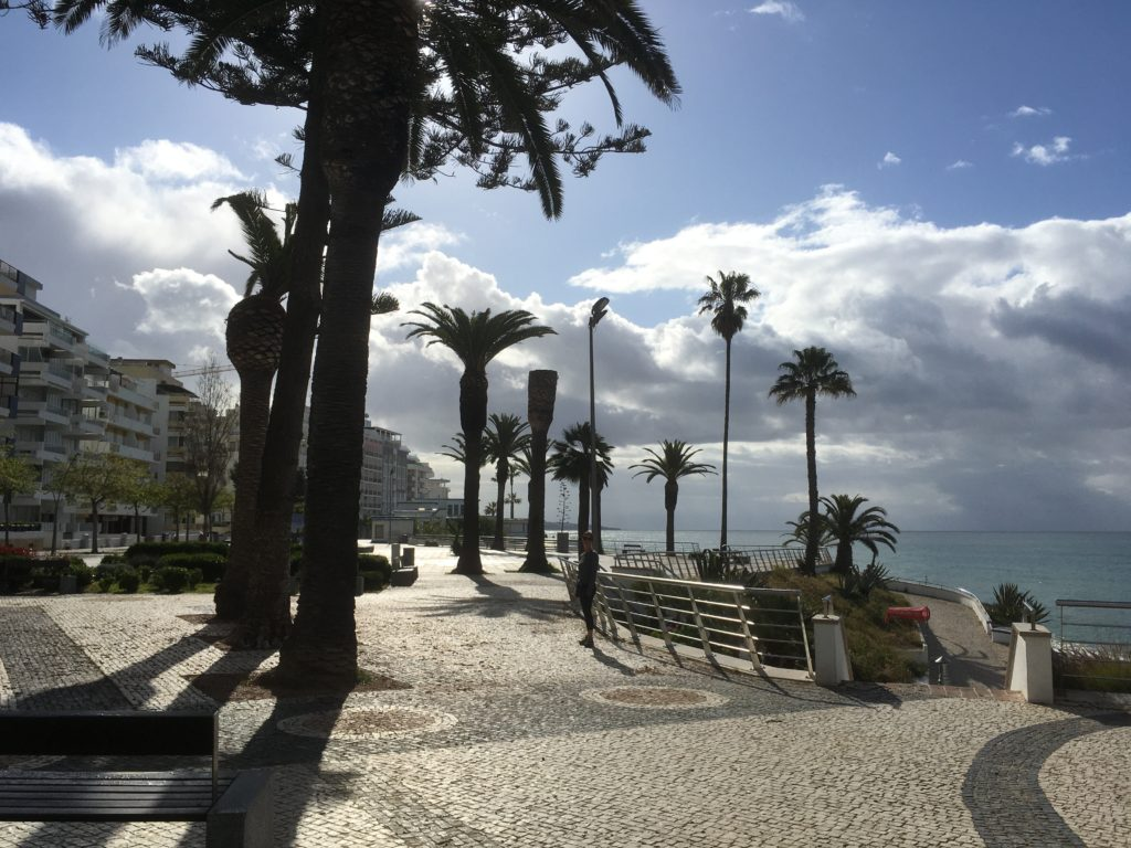 The Armacao de Pera malecon with view of the ocean and palm trees