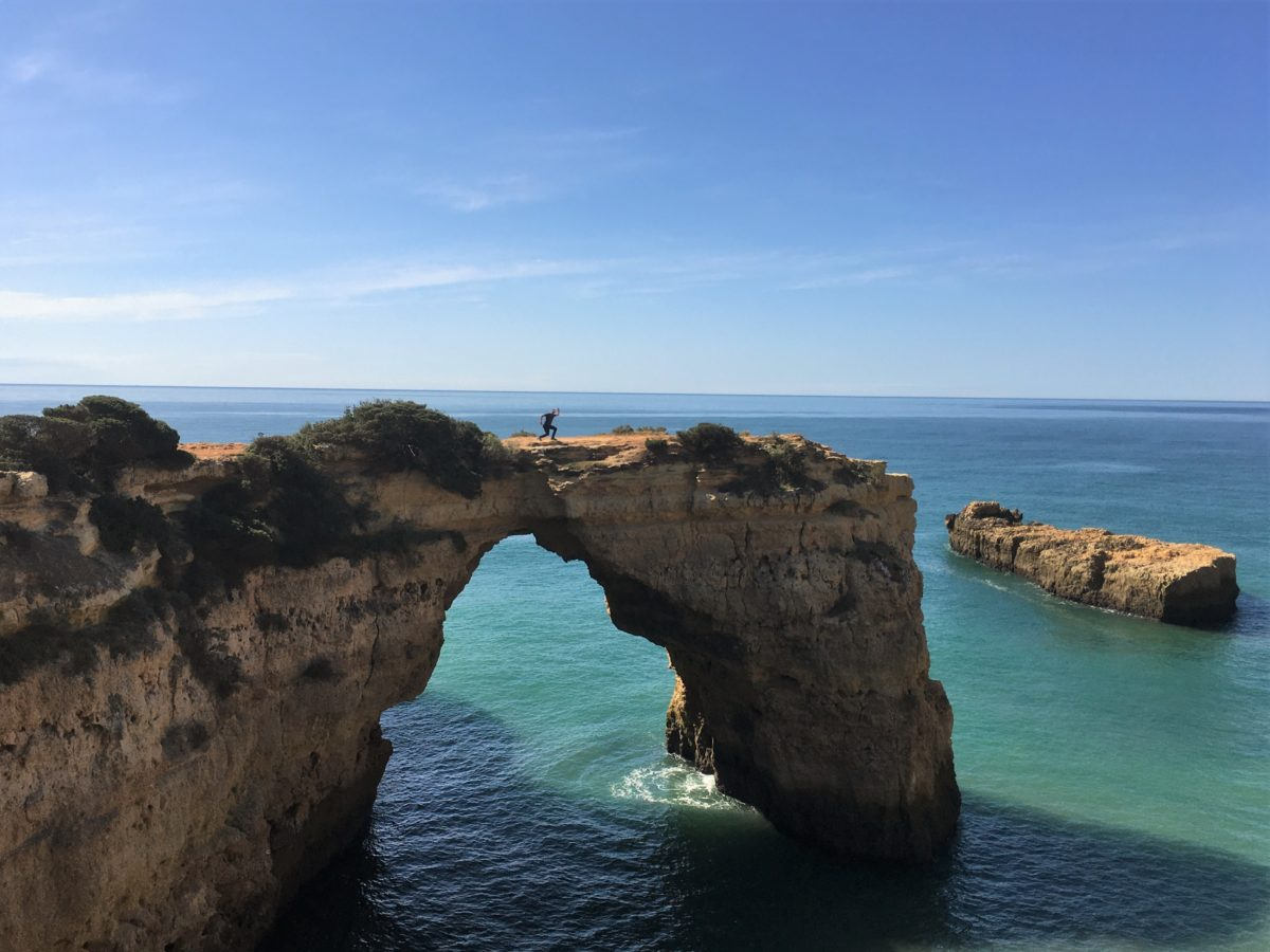 Man on rock arch at Praia Albaneira Algarve Portugal