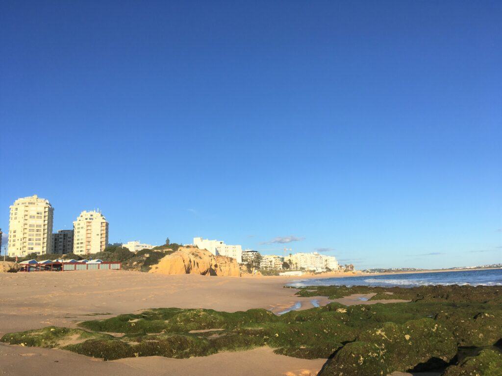 Beach with the white buildings of Armacao de Pera Portugal in the distance