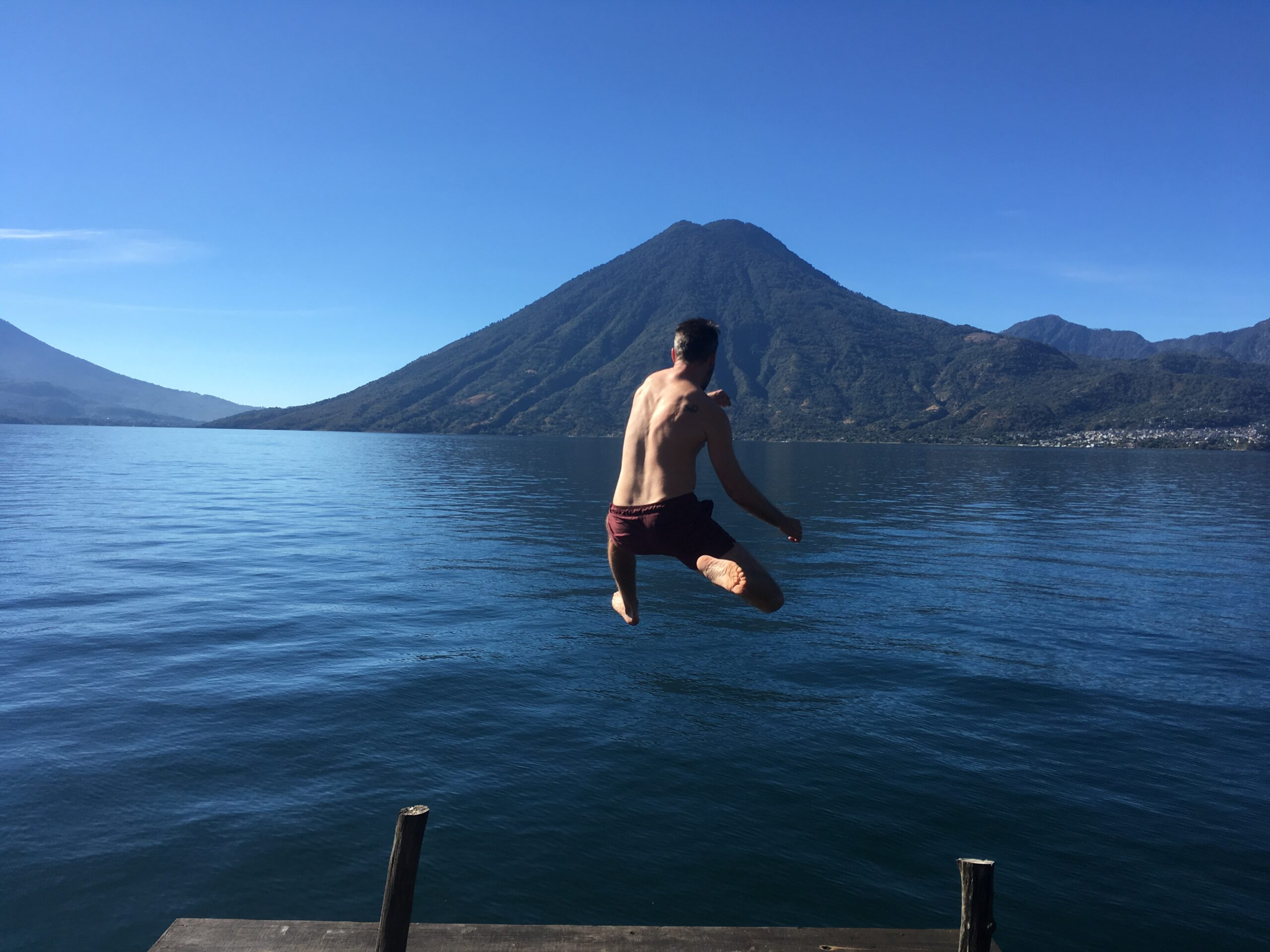 Person jumping into water with volcano in the back at lake atitlan