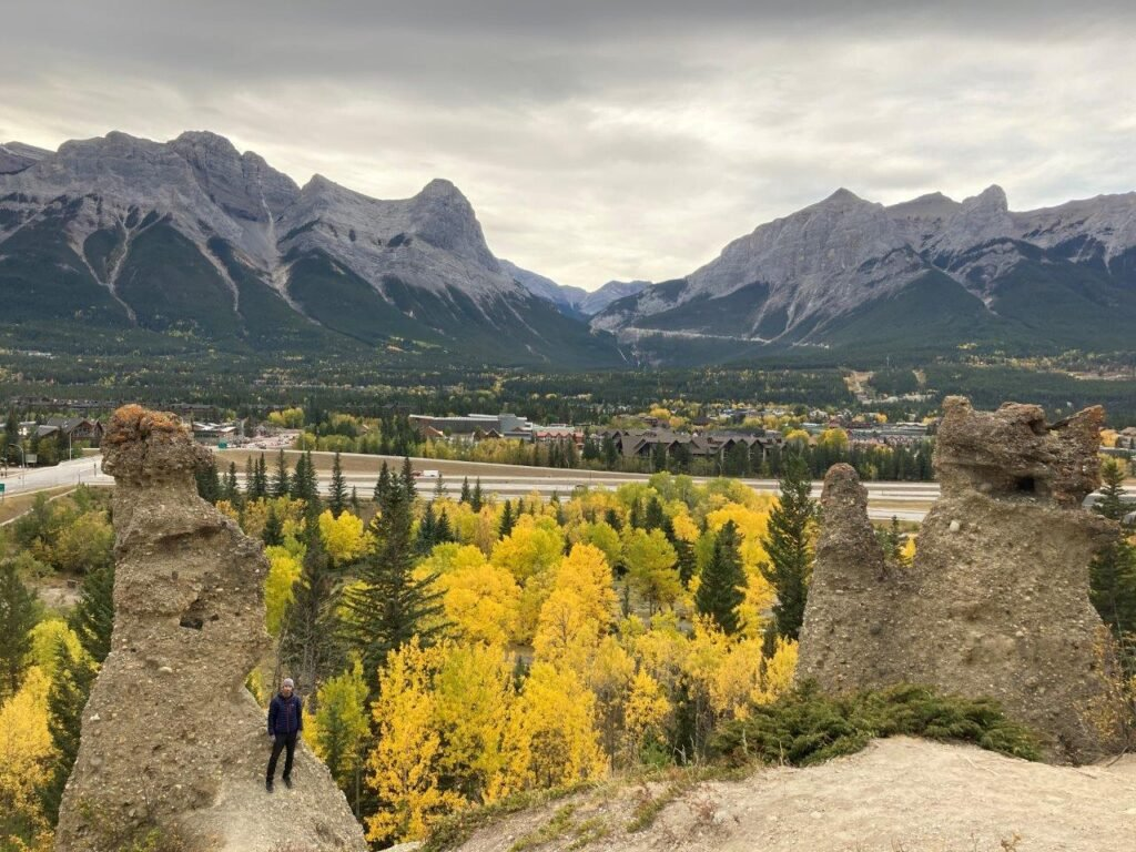 Hoodoos with trees with yellow leaves and mountains in the background on one of the best easy hikes Canmore offers.