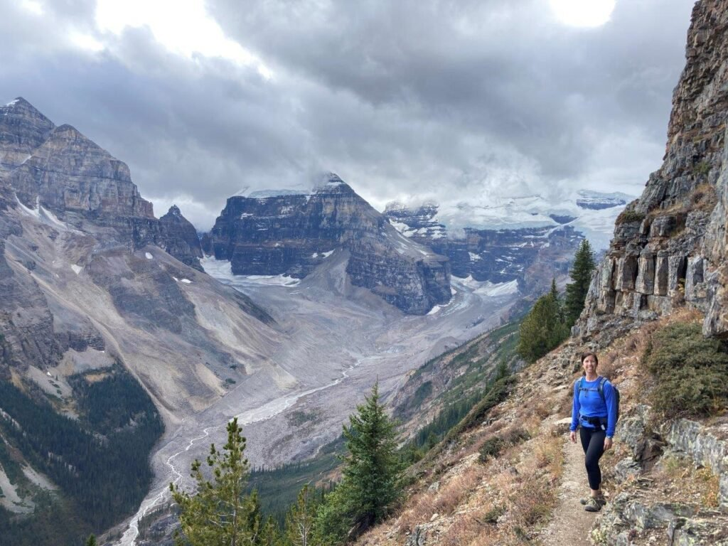 Hiker on trail beside valley with glaciers at the end