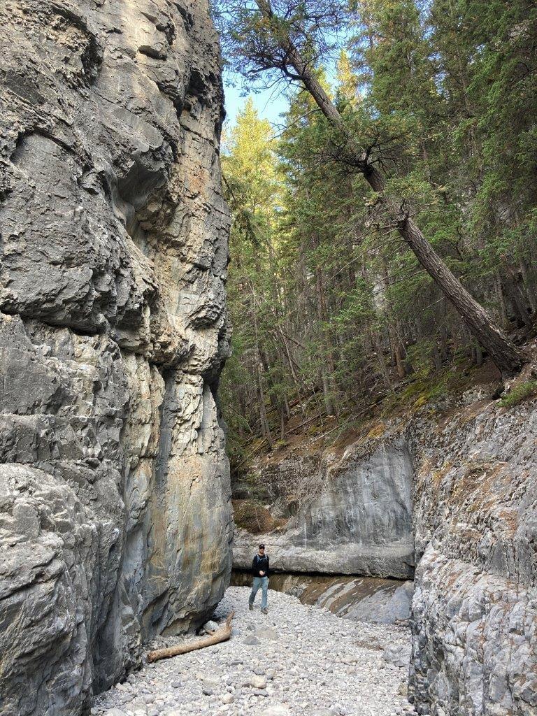 Man walking beside tall rock face
