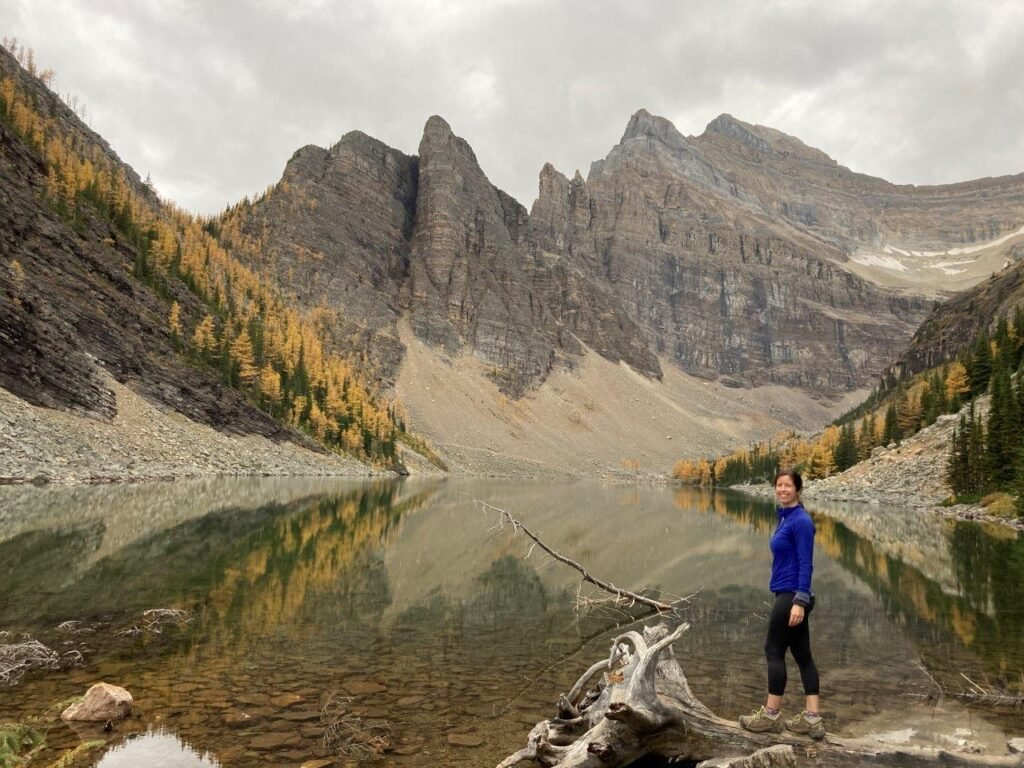 Reflections of mountains and larch trees on Lake Agnes