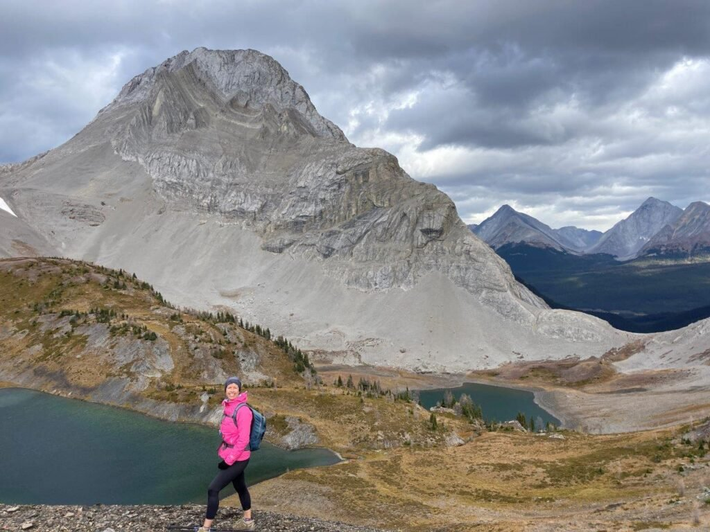 Girl in pink coat, two lakes and a mountain on Smutwood Peak trail, one of the best hikes Canmore has