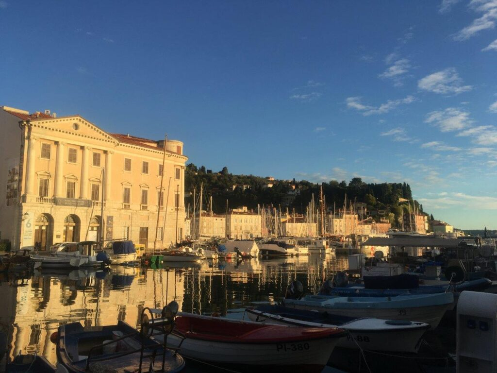 The light of the setting sun on the buildings behind the port of Piran Slovenia