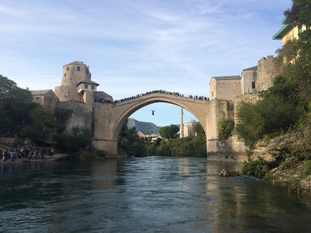 Person in midair after jumping off the Mostar bridge