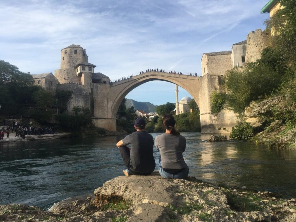 Two people looking at the Old Bridge sitting on a rock