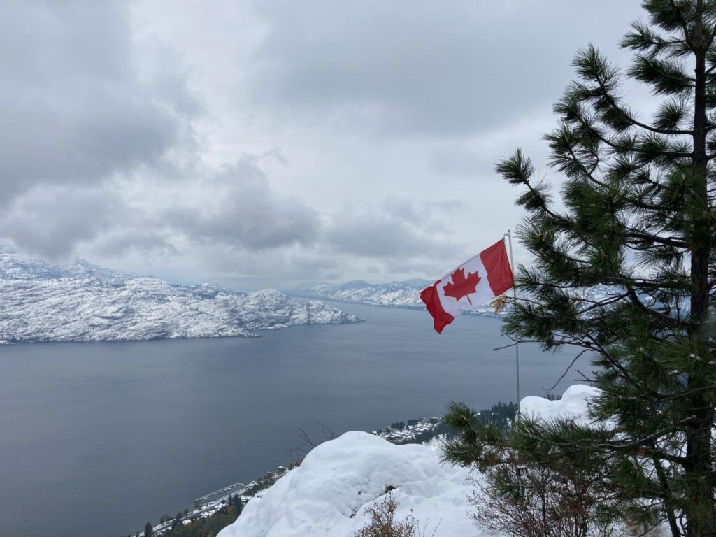 Canadian flag on viewpoint over large lake on one of the best hikes Kelowna has