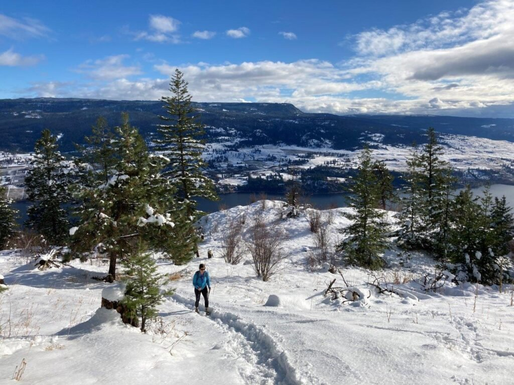 Hiker on a snowy path with a lake in the background on one of the best hikes Kelowna has
