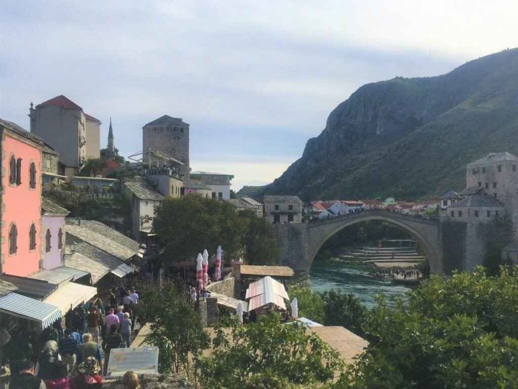 View of pedestrian street crowded with tourists and the Mostar Bridge