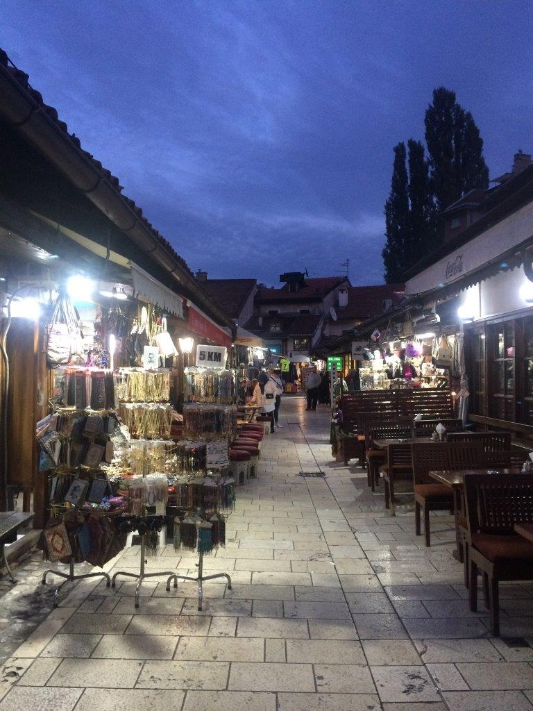 A narrow street with tourist shops and tables from restaurants