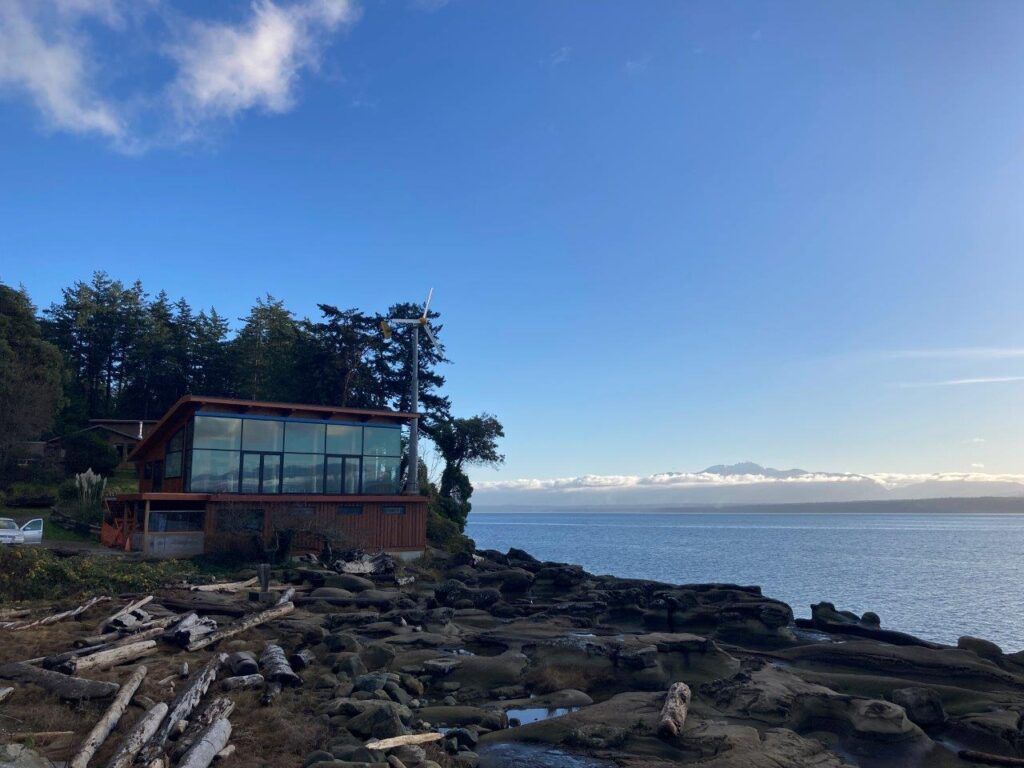 A glass fronted restaurand with rocks out front and ocean to the side at Hornby Island camping site of Ford's Cove