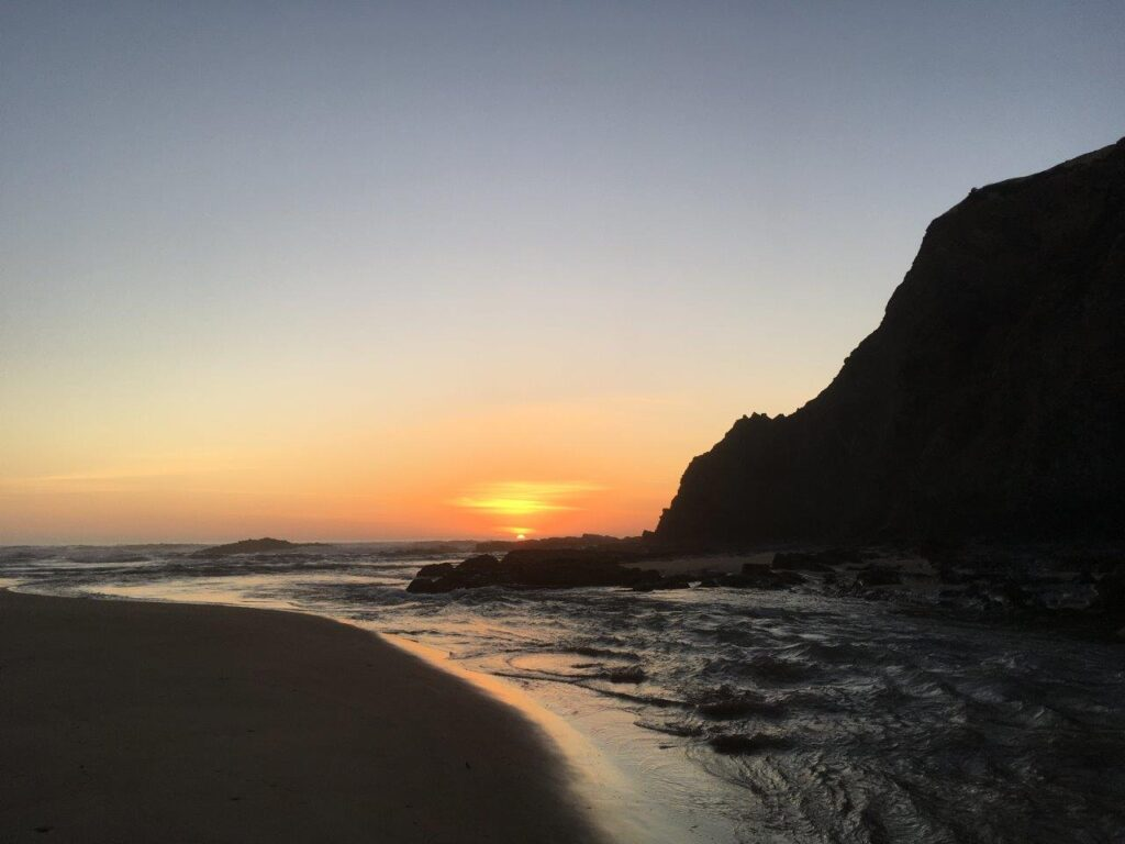 Sunset from the Praia de Odeceixe including a river and cliffs