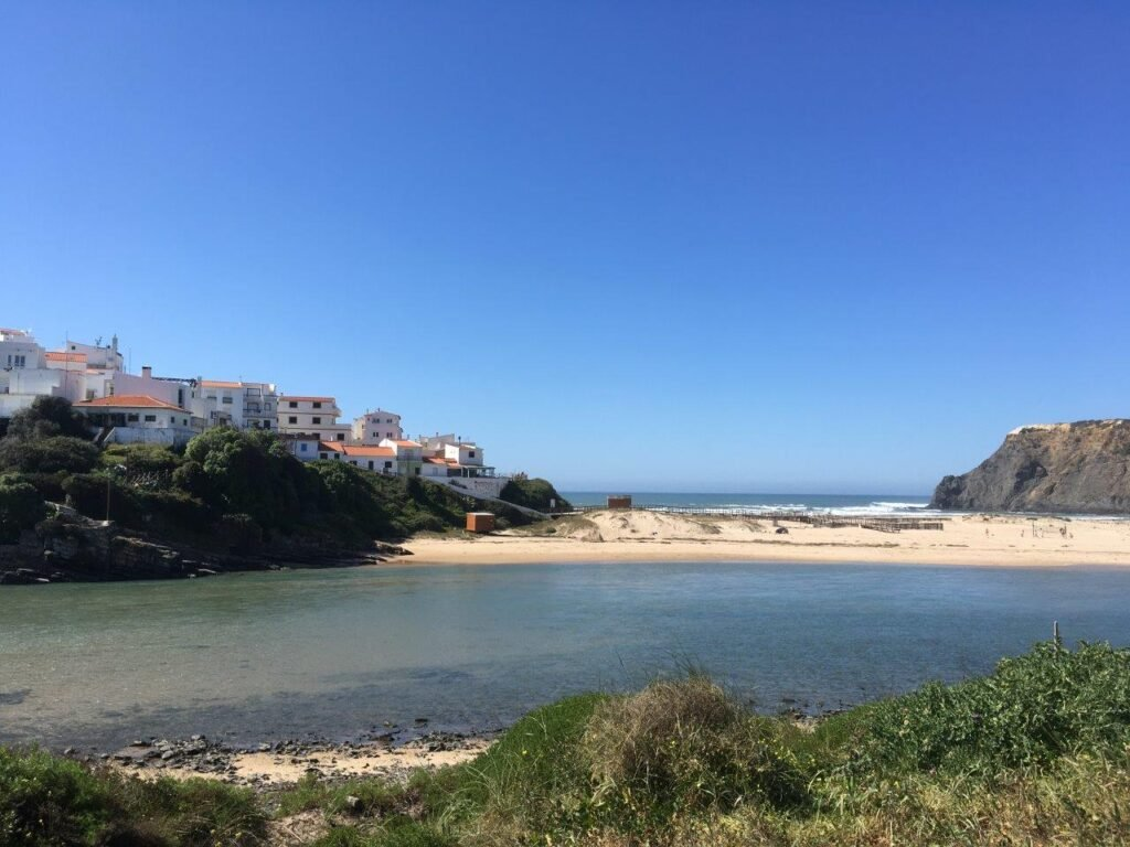 The red roofs of the white buildings at Priai de Odeceixe Mar from across the river