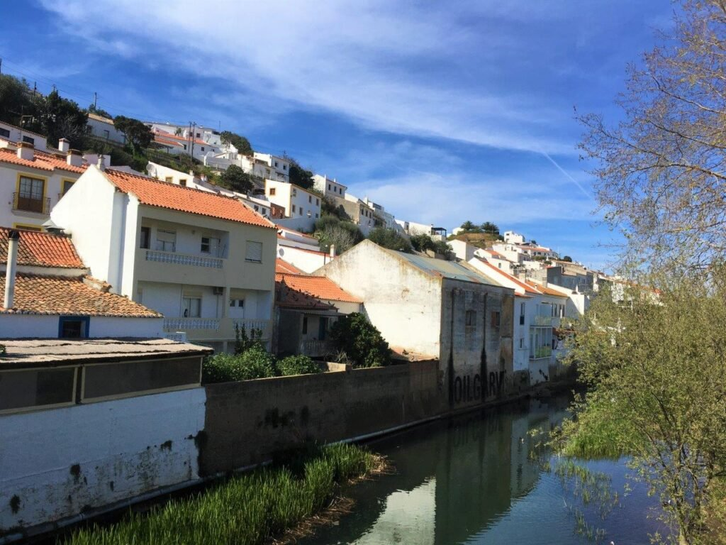 The buildings of the old town of Aljezur along a river