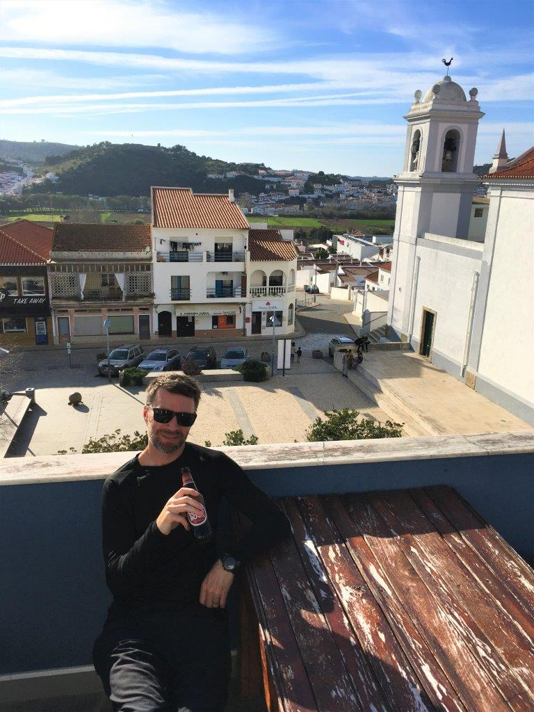 Man on deck overlooking Aljezur Portugal main square and chruch