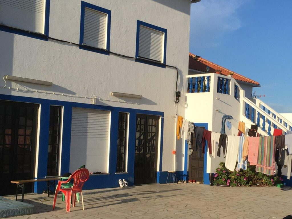 Local blue and white house in Almograve Portugal with a clothes line out front