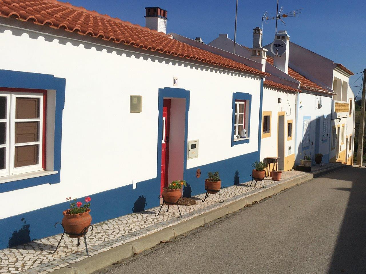 White buildings with blue and yellow trim in traditional Almograve Portugal