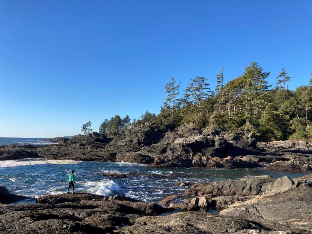 Woman walking along exposed rocks at low tide at Botanical Beach Provincial Park