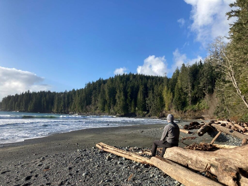 Man sitting on drifwood looking out to the ocean on China Beach BC