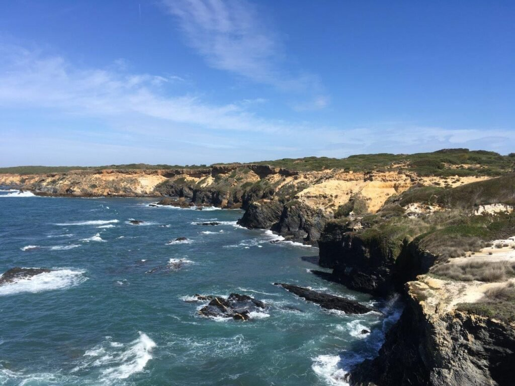 Tall cliffs with sand dunes on top and ocean below near Almograve Portugal
