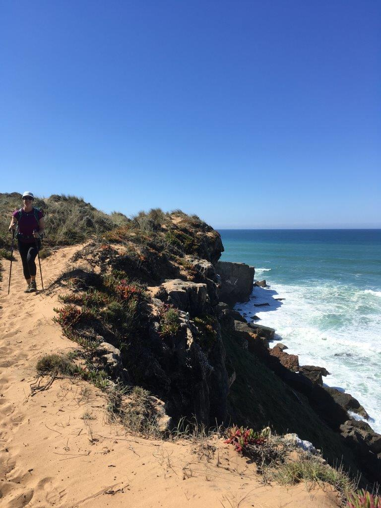 Hiker on cliff on sandy trail on Rota Vicentina