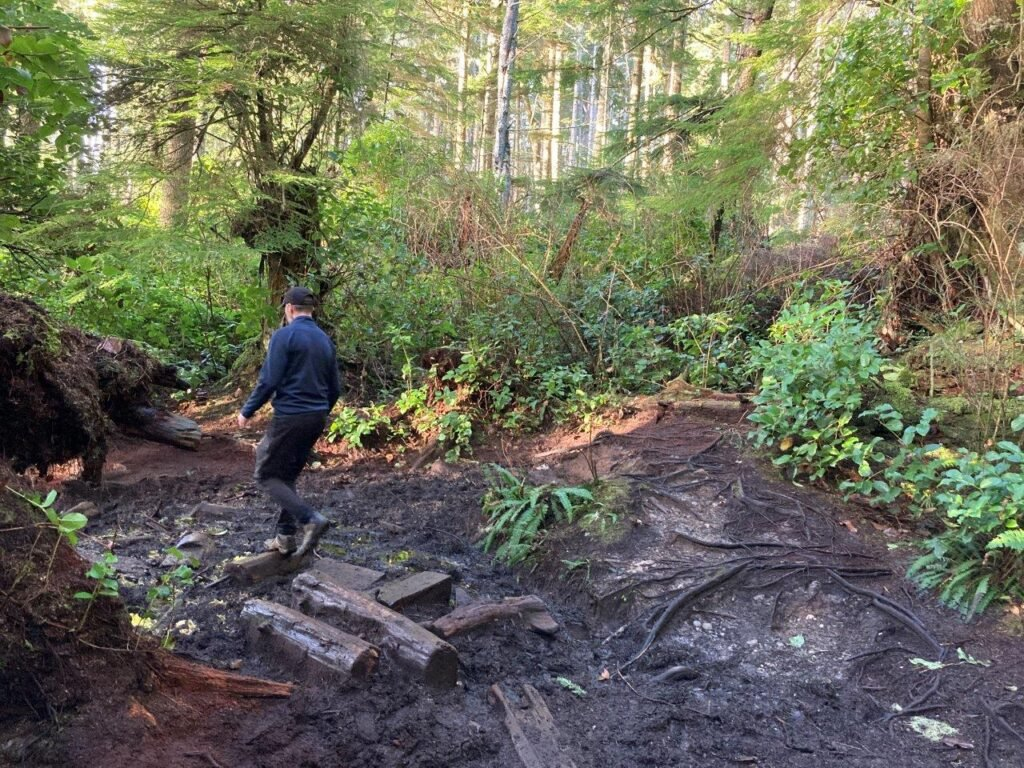 Man walking through muddy section on trail to Mystic Beach Vancouver Island