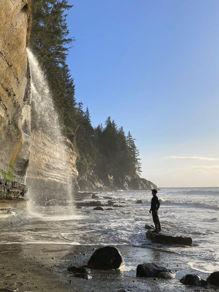 Man standing on rock looking at waterfall at Mystic Beach Vancouver Island
