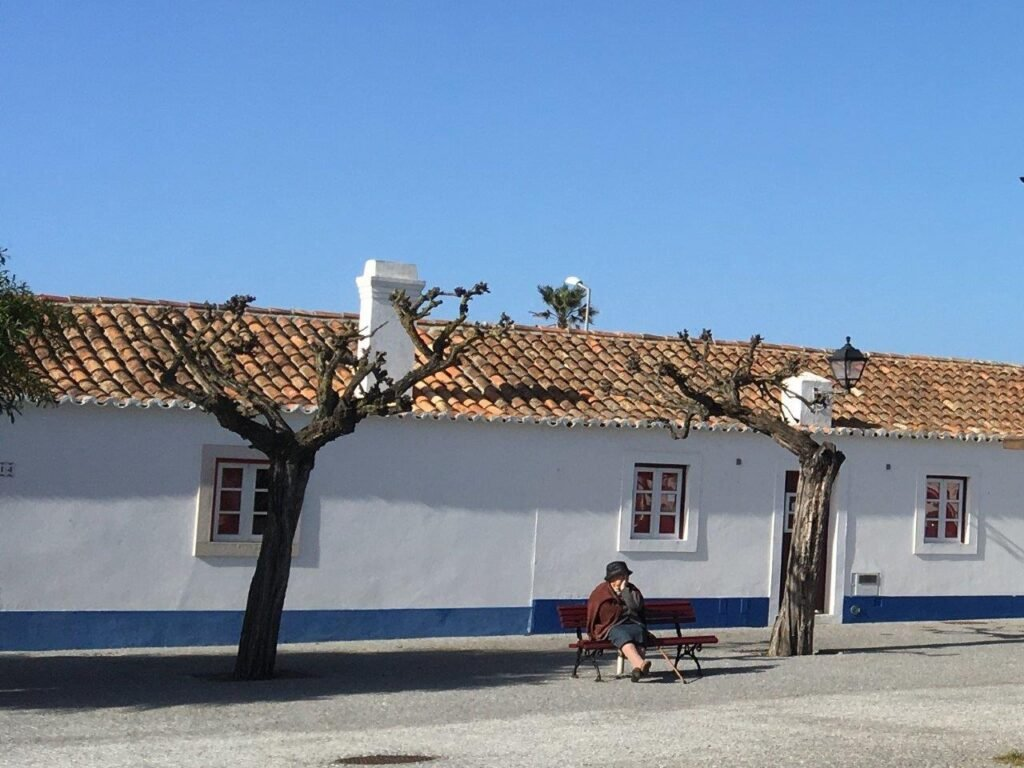 Local woman sitting on bench in front of white building in Porto Covo Portugal