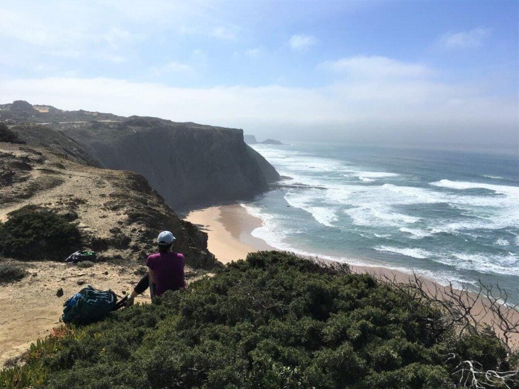 Woman sitting on cliff overlooking Praia da Fateixa near Aljezur Portugal